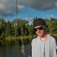 Ben Wiltsie displays a crayfish that grabbed his lure while he was fishing for pike in Lake of the Woods, near Kenora, Ontario, Canada.