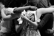 Connor Cook, 16, looks out from the program for his memorial service as his classmates Maia Lavoy, 15, left, Natalie Mitchell, 15, middle, and Aibhlin Moye-Linehan, 16, embrace in the Thetford Academy gym in Thetford, Vt., Saturday, July 7, 2012. Cook died June 27 after being struck by lightning while working in the fields on Crossroads Farm in Post Mills four days earlier. <br /> Valley News - James M. Patterson