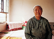 Old woman in her house at Desert Control project at Guancai  Village. Ningxia Province, China.