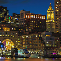 Sail Boston tall ships Europa and Atyla moored in the Boston Harbor waterfront skyline photography art  from New England photographer Juergen Roth. The image shows the historic sailboats in front of the Boston Financial Waterfront District landmarks such as the Custom House of Boston, One International Place, Boston Harbor Hotel with its icondic photographed on a beautiful summer sunset evening. <br />