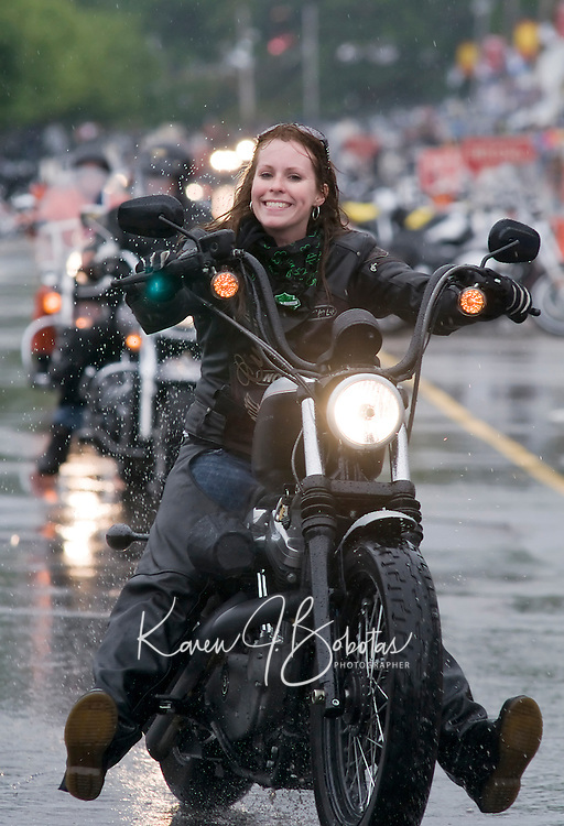 "The rain didn't dampen the ""spirit"" of this biker as she made her way up Lakeside Avenue in Weirs Beach during Motorcycle Week.  (Karen Bobotas Photographer)"