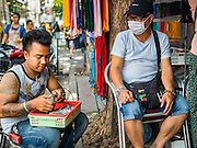 27 NOVEMBER 2015 - BANGKOK, THAILAND:  A street vendor puts together an amulet in his market stall while he chats with another vendor. Hundreds of vendors sell amulet and Buddhist religious paraphernalia to people in the Amulet Market, a popular tourist attraction along Maharat Road north of the Grand Palace near Wat Maharat in Bangkok. Bangkok municipal officials announced that they are closing the market and forcing vendors to relocate to an area about one hour outside of Bangkok. The closing of the amulet market is the latest in a series of municipal efforts to close and evict street vendors and markets from areas that have potential for redevelopment. The street vendors will be evicted from the area by Sunday, Nov. 29.   PHOTO BY JACK KURTZ