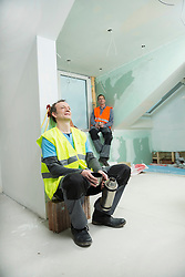 Two construction workers at construction site of new building having a break