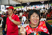 01 MAY 2013 - BANGKOK, THAILAND: A Thai Red Shirt with a Yingluck Shinawatra pen and photos of former Prime Minister Thaksin Shinawatra and current Prime Minister Yingluck Shinawatra (she is Thaksin's sister) at a Red Shirt rally at the Thai Constitutional Court. Several hundred Thai Red Shirts, members of the United Front for Democracy against Dictatorship (UDD), have been camped out at Thailand's Constitutional Court, which oversees matters related to the Thai constitution and constitutional amendment. The Red Shirts are protesting the court's decision to consider a petition regarding the constitutionality of the constitutional amendments that have been proposed by the government. The group is arguing that by considering the petition, the Court is impeding the powers of the legislative branch.   PHOTO BY JACK KURTZ