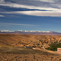 Africa, Morocco, Skoura. Moroccan desert village and snow-capped Atlas mountain range.