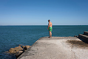 A lone bather looks over the edge of the artificial pier at Estoril near Lisbon, Portugal.