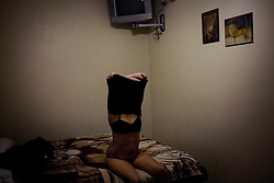 A prostitute undresses for a client in a short term motel in Nogales, Sonora.