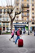 Walking with suitcases on the Nova Rambla, Tarragona, Catalonia, Spain.