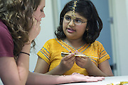 Bollywood Dance student Arika Diwedi, 10, talks with volunteer Rachel Voor, 21, over a henna tattoo during the English Conversation Club: Dance and Dialogue event Saturday April 9, 2011 at the Iroquois Branch of the Louisville Free Public Library in Louisville, Ky. Henna and Bindi followed the Bollywood dance lesson, and then volunteers were paired with English language learners to work on conversation skills. (Photo by Brian Bohannon)