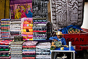 A man sells pineapples from his pickup truck during the patron saint festival at San Pedro Chenalho, a Tzotzil Mayan village outside San Cristobal de las Casas, Chiapas, Mexico on June 27, 2008. Large rugs with gawdy designs surround his small table.