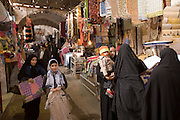 All manner of goods can be found in the bazaars of Iran but this is also a meeting place for local residents. Women in black chador (tent) converse in the warren-like covered Yazd Bazaar. Yazd, Iran.