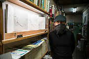 portrait of curator Masamichi Tamura with his Tana gallery bookshelf concept project in Tokyo Japan