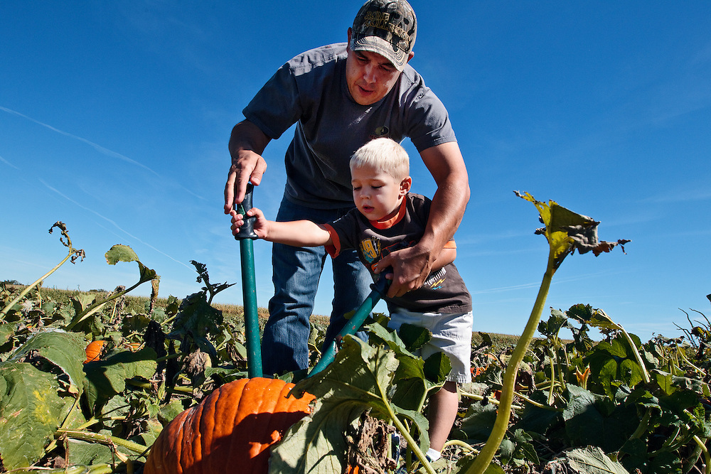 Tony Supik helps his three-year-old son Isaac pick a pumpkin Sunday afternoon at the ScareCrow Patch in St. Libory. (Independent/Matt Dixon)