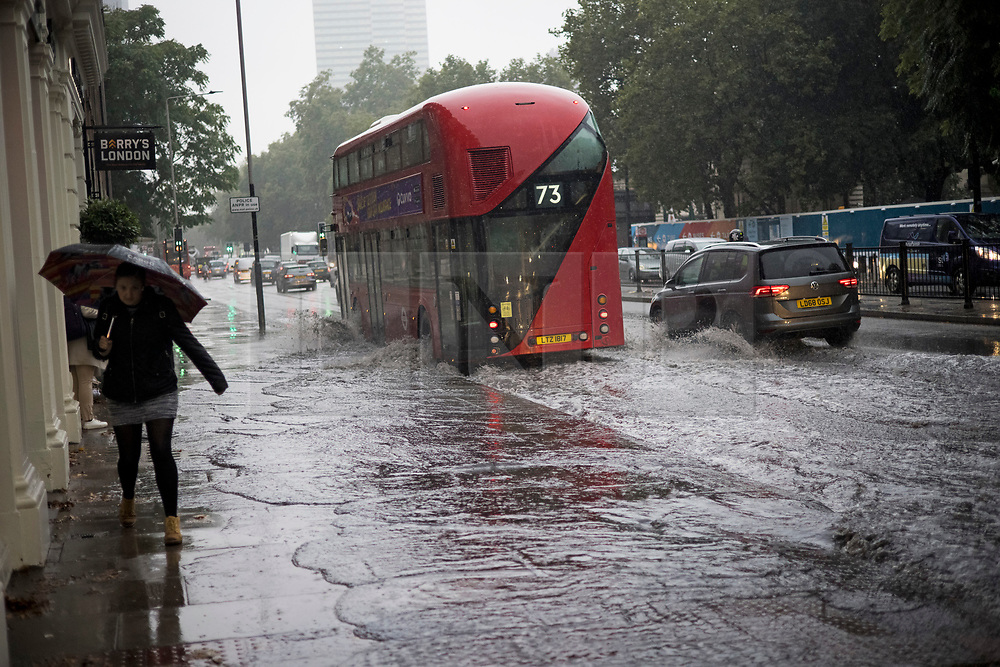 © Licensed to London News Pictures. 14/09/2021. London, UK. A bus pushes a wave of water on to a footpath as it drives through deep surface water on the Euston road in North London during heavy rainfall. Heavy rain is expected to cause flash flooding in parts of the UK. Photo credit: Ben Cawthra/LNP