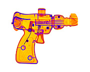 An X-ray of a confetti gun. This gun shoots streamers of confetti at a party.  The shell of confetti can be seen above the trigger.