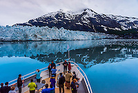 "Passengers aboard the Un-Cruise  ""Wilderness Explorer"" view the Margerie Glacier from the bow of the boat, Glacier Bay National Park, southeast Alaska USA."