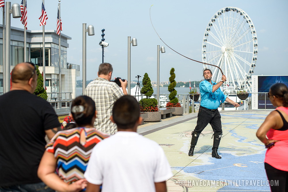 A cowboy street performer cracks a whip at National Harbor in Maryland, on the banks of the Potomac near Washington DC. In the background is the giant ferris wheel.