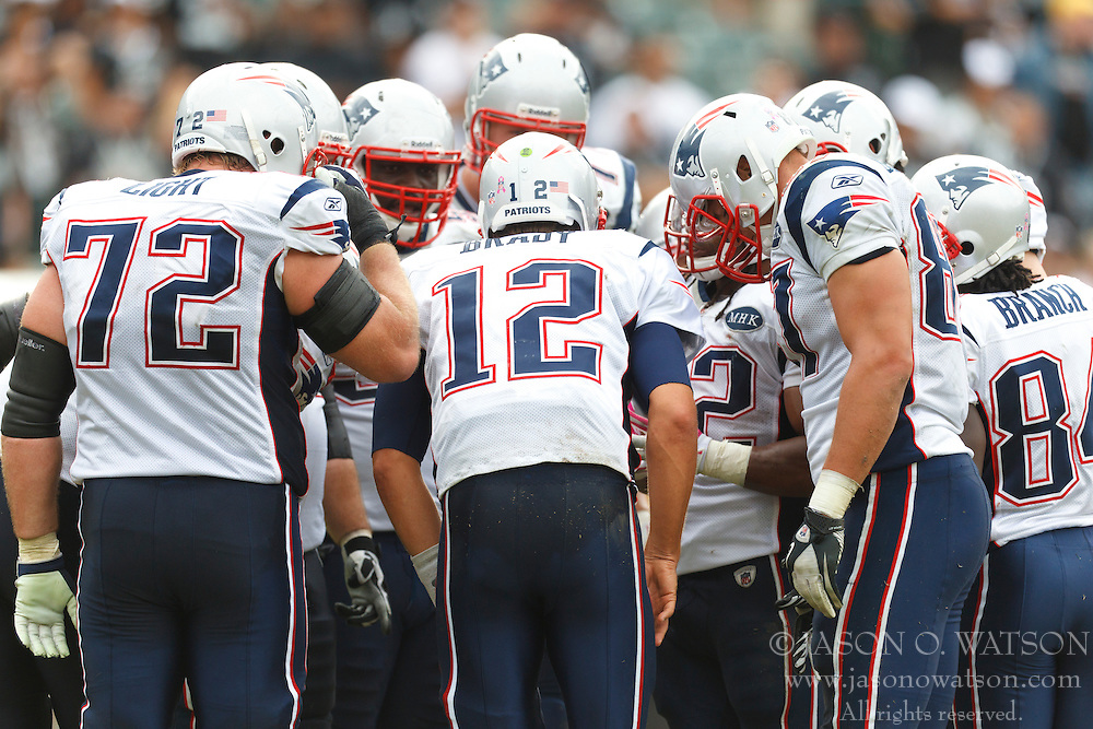 Oct 2, 2011; Oakland, CA, USA; New England Patriots quarterback Tom Brady (12) calls a play in the huddle against the Oakland Raiders during the fourth quarter at O.co Coliseum. New England defeated Oakland 31-19. Mandatory Credit: Jason O. Watson-US PRESSWIRE