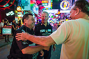 """26 SEPTEMBER 2014 - PATTAYA, CHONBURI, THAILAND: Members of the Foreign Tourist Police Assistants (FTPA) talk to an Italian tourist on Walking Street in Pataya. The FTPA assist local police in dealing with foreign tourists but don't have arrest powers. Pataya, a beach resort about two hours from Bangkok, has wrestled with a reputation of having a high crime rate and being a haven for sex tourism. After the coup in May, the military government cracked down on other Thai beach resorts, notably Phuket and Hua Hin, putting military officers in charge of law enforcement and cleaning up unlicensed businesses that encroached on beaches. Pattaya city officials have launched their own crackdown and clean up in order to prevent a military crackdown. City officials have vowed to remake Pattaya as a """"family friendly"""" destination. City police and tourist police now patrol """"Walking Street,"""" Pattaya's notorious red light district, and officials are cracking down on unlicensed businesses on the beach.     PHOTO BY JACK KURTZ"""