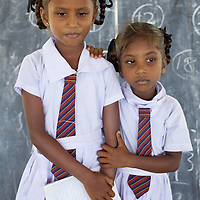 Conflict-affected sisters T. Chandrakumari, age 9, and T. Valarmath, age 5, in a UNICEF-supplied Temporary Learning Space at Vadamunai Government Tamil Mixed School in Batticaloa District. <br /> <br /> When fighting between the LTTE and Colombo Government forced the displacement of the local Tamil community in 2007, the Vadamunai Government Tamil Mixed School in Batticaloa District was closed. Since reopening in January 2009, the school has six teaching staff for 88 pupils from Grades 1-9. Before closure,136 pupils studied at the school. Poor road-infrastructure and the remote location of the school means that many staff have to commute for more than three hours. Five classes are held in a UNICEF-supplied Temporary Learning Space. Four other classes are conducted outside, beneath trees. Many of the students suffer with the trauma and stress associated with those living in conflict situations. The staff must deal with these issues as well as the personal difficulties that they themselves suffer living in a conflict environment. To further antagonise an already difficult situation, the school suffers the very real danger of wild-elephant encroachment on their grounds. The school encourages gender-equality and has a meals program, providing some students their only square meal in the day. <br /> <br /> Photo: Tom Pietrasik<br /> Batticaloa District, Sri Lanka<br /> September 30th 2009
