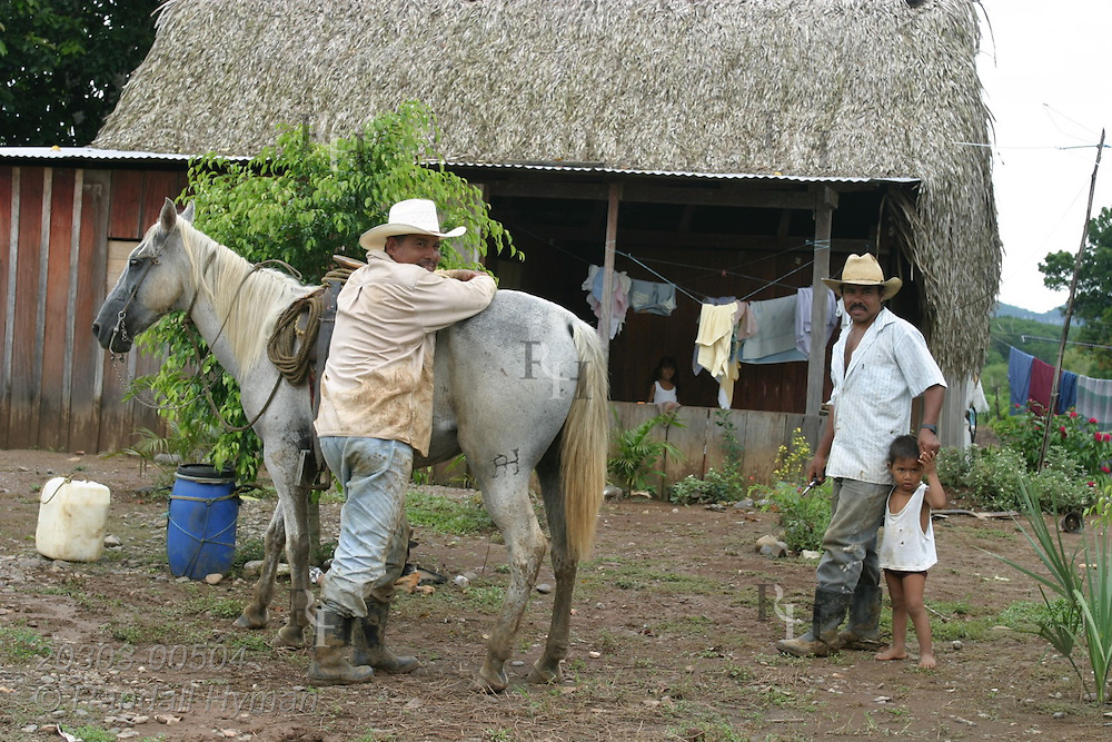 Two men and young boy stand by horse outside thatched roof shack in a remote area of poverty-plagued Uxpanapa Valley of southern Veracruz; Mexico.