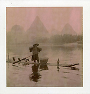 Polaroid Chocolate. Picture of a fisherman on Li river. He wears a coat made of bark, has a conic hat. he is standing on his small bamboo raft, holding a pole in his hand. There are some cormorants stand on his raft too. He brings them along. Fisherman uses them to fish. He has a big basket to keep all fishes caught by the birds. the landscape is mountainous in background. Li river, Guangxi province, China, Asia.