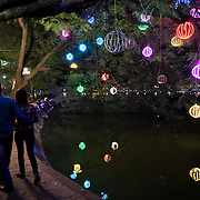 A couple strolls along the lakefront of Hoan Kiem Lake in central Hanoi in the evening, admiring illuminated balls hanging from the trees.. The lake is known in Vietnamese as Ho Hoan Kiem, it means Lake of the Returned Sword.