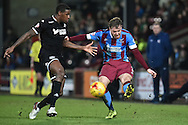 Scott Laird of Scunthorpe United crosses ball against Donervon Daniels of Wigan Athletic   during the Sky Bet League 1 match between Scunthorpe United and Wigan Athletic at Glanford Park, Scunthorpe, England on 2 January 2016. Photo by Ian Lyall.
