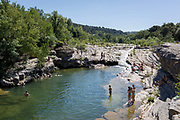 Bathers swim in the natural waters of the River Orbieu flowing through rocky gorge, on 24th May, 2017, in Ribaute, Languedoc-Rousillon, south of France