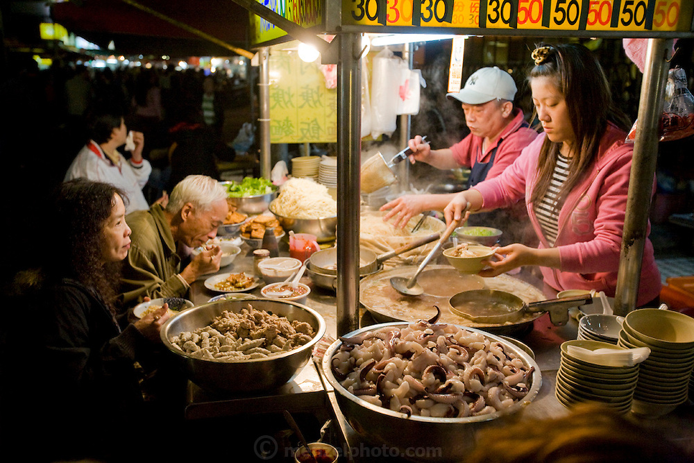 A vendor prepares a meal for a customer at an open air food stall in Taipei, Taiwan.