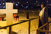 Moscow, Russia, 18/01/2014.<br /> A priest with a cross made of blocks of ice as Orthodox Christian believers celebrate Epiphany at a lake in southern Moscow. Priests blessed the waters and followers baptised themselves by total immersion in the freezing lake in temperatures of minus 18C.