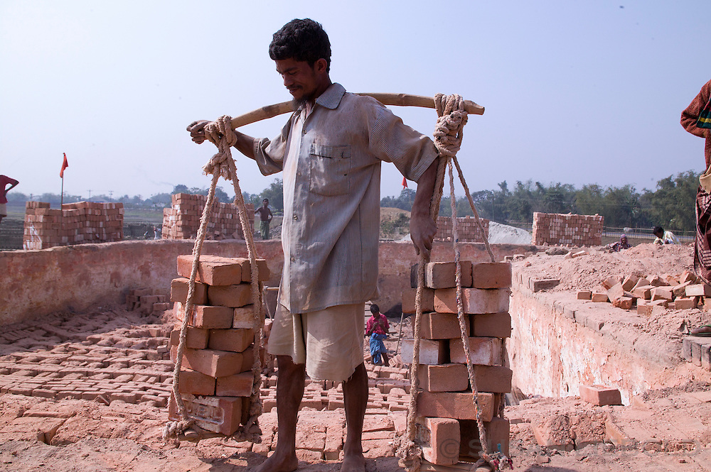 Man at a brick making factory in Bangladesh carrying a heavy load of bricks over his shoulders.