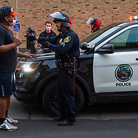 A protester pleads with Syracuse police to hold off on enforcing Mayor Walsh's curfew on Protesters defying the order Sunday night, May 31, 2020 where they took a stance in front of the Justice Center on State Street to protest the death of George Floyd in Minniapolis last Memorial Day.