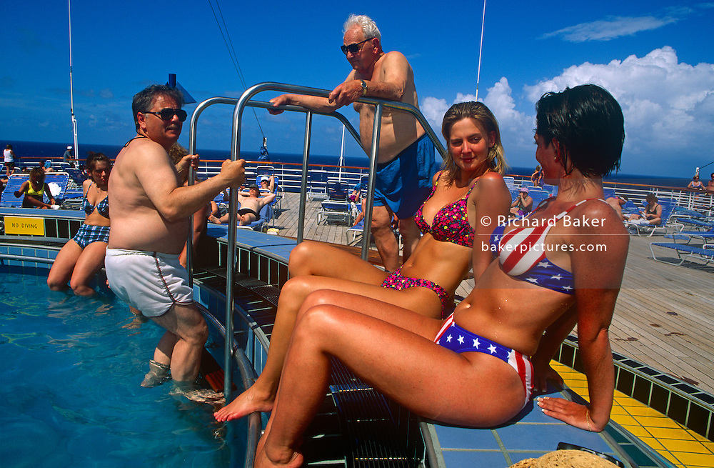 Half-way across the Gulf of Mexico, between Miami and Cancun in Mexico, two of Carnival Cruise's Fun Ship Ecstasy's female passengers are at a small circular pool on the Sun Deck to enjoy the first few days sailing on the tropical seas. The two girl friends frolic around the poolside exposing, tanned skin under a baking hot tropical sun at its zenith, directly overhead at mid-day. Carnival's ships are known for their Las Vegas decor and entertainment, calling its vessels Fun Ships. One young lady  wears a bikini featuring a patriotic Stars and Stripes. The MS Ecstasy is a Fantasy class cruise ship featuring two pools, whirlpools, a variety of dining options, nightclubs, a casino, and duty-free shopping.