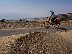 Woman cycling on road by sand dune and sea