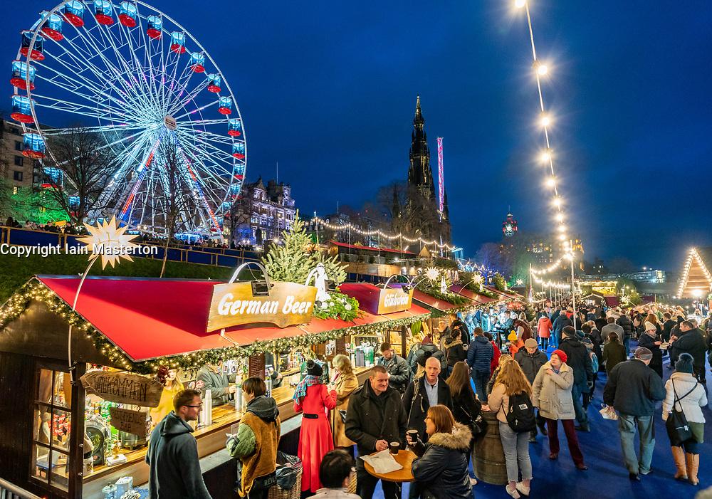Crowds of people in busy Edinburgh Christmas Market in West Princes Street gardens in Edinburgh, Scotland, UK