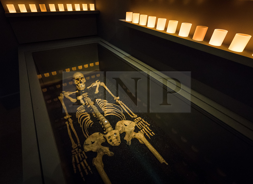 © Licensed to London News Pictures. 27/01/2016. LONDON, UK.  The skeleton of  one of 13 victims of the Black Death, who were recently excavated when the Crossrail project clipped the corner of Charterhouse Square lies in a glass case in the new museum lit by electric candles. London's Charterhouse, a former 12th-century Carthusian monastery and burial ground for victims of the Black Death, opened its doors to the public for the first time in 400 years today, including the opening of a new museum.  Photo credit: Vickie Flores/LNP