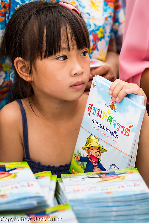 """23 APRIL 2013 - BANGKOK, THAILAND:   A Thai girl waits to donate a book to a Thai literacy project during the opening ceremony to mark Bangkok as the World Book Capital City 2013. UNESCO awarded Bangkok the title. Bangkok is the 13th city to assume the title of """"World Book Capital"""", taking over from Yerevan, Armenia. Bangkok Governor Suhumbhand Paribatra announced plans that the Bangkok Metropolitan Administration (BMA) intends to encourage reading among Thais. The BMA runs 37 public libraries in the city and has modernised 14 of them. It plans to build 10 more public libraries every year. Port Harcourt, Nigeria will be the next World Book Capital in 2014..PHOTO BY JACK KURTZ"""