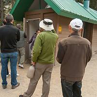 Tourists wait their turn at a public restroom in Banff National Park, Alberta, Canada.