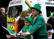 Man with in green clothes with kids on bicycle, Dublin, St. Patrick's Day, 2009