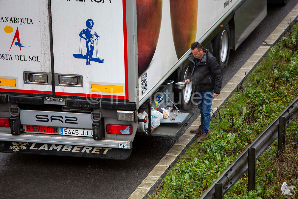 A driver makes himself a cup of tea as freight lorries line up in queues contained in Operation Stack on the M20 motorway at Ashford, Kent, United Kingdom on the 23rd of December 2020. Truck drivers have been waiting in operation stack on the M20 motorway for over 48 hours now, France closed it's boarders with the UK after a new faster spreading strain of the COVID-19 virus broke out in Kent.