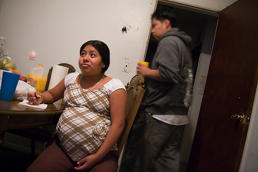 Eduardo Leon leaves for work as his wife Marcela watches television in their studio apartment in Swan Lake, New York on October 11, 2008. Leon, who immigrated from Puebla state, Mexico to upstate New York to join his parents and siblings, works every day at Hudson Valley Foie Gras in Ferndale while his wife, expecting a child, stays home.