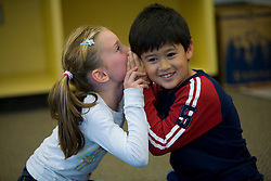 United States, Washington, Bellevue, girl (age 7) telling secret to boy in classroom.  MR