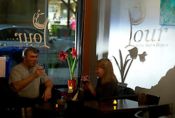 A couple enjoys a glass of wine at Pour Wine Bar and Bistro, in the Montclair district of Oakland, Calif., Wednesday, Dec. 23, 2015. (Photo by D. Ross Cameron)