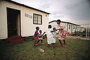 The Qampie children and a few of their friends play 'ring around the rosie? on a Sunday afternoon in front of their house in Soweto, South Africa. The Qampie family lives in a 400 square foot concrete block duplex house in the sprawling area of Southwest Township (called Soweto), outside Johannesburg (Joberg) South Africa. Child, Games. Material World Project.