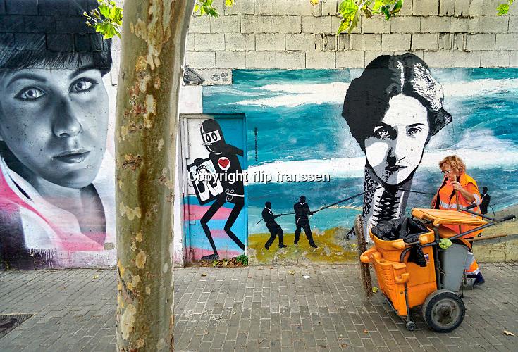 Spanje, Valencia, 3-11 2019  Graffiti, muurschildering  in het centrum, stadscentrum, van de stad . Een vrouw die werkt voor de gemeentereiniging, gemeentelijke reinigingsdienst, loopt voorbij .Foto: Flip Franssen