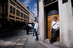 © London News Pictures. 04/09/2013. London, UK. A man shades his eyes from the suns light reflecting off 20 Finchurch Street in the financial district of central London. The building, which has been named unofficially the 'Walkie Talkie' building because of its shape, intensifies the suns light and reflects it onto the street below. There have been reports of damage to vehicles and local shops caused by the heat of the reflected light. Photo credit: Ben Cawthra/LNP