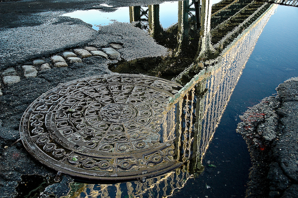 Reflection of the Manhattan Bridge in a puddle in DUMBO, Brooklyn, New York, 2008.