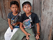 """Sept. 27, 2009 -- TAK BAI, THAILAND: Thai Muslim boys play with toy shotguns in front of their home in Tak Bai, Narathiwat, Thailand. Thailand's three southern most provinces; Yala, Pattani and Narathiwat are often called """"restive"""" and a decades long Muslim insurgency has gained traction recently. Nearly 4,000 people have been killed since 2004. The three southern provinces are under emergency control and there are more than 60,000 Thai military, police and paramilitary militia forces trying to keep the peace battling insurgents who favor car bombs and assassination.   Photo by Jack Kurtz / ZUMA Press"""