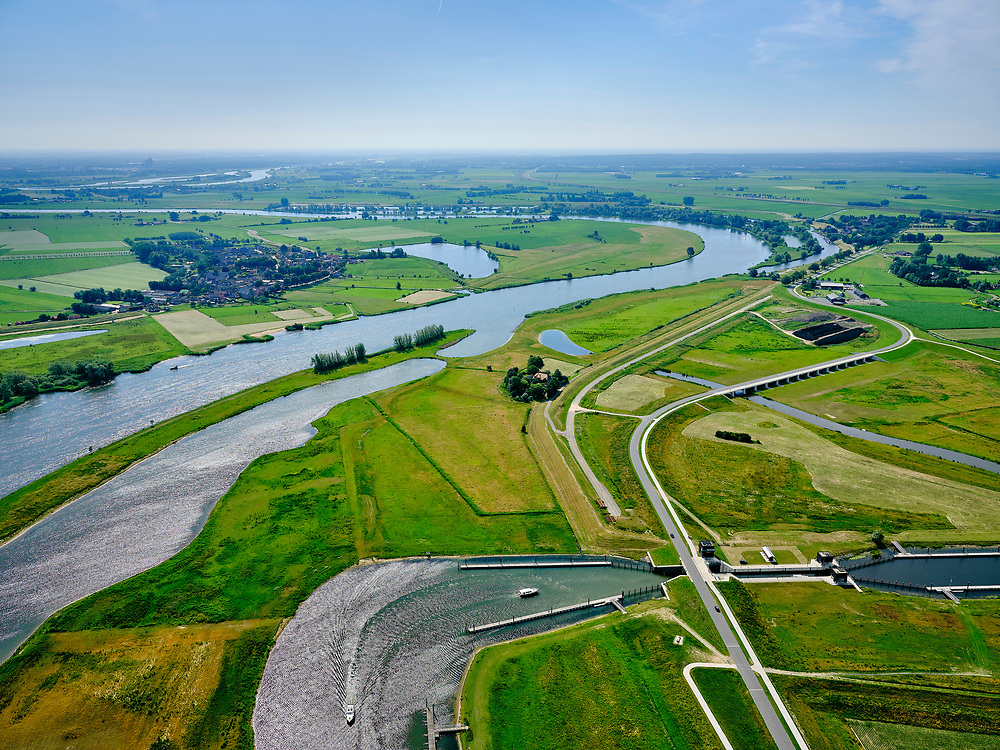 "Nederland, Overijssel, Gemeente Kampen; 21–06-2020; zicht op de IJssel ter hoogte van Wilsum met de Onderdijkse Waard. Voorgrond de Scheeresluis, recreatieschutsluis en ingang voor de pleziervaart van het Reevediep. Midden rechts het inlaatwerk van het nieuw aangelegde Reevediep,  Het Lange End.<br /> Het Reevediep is aangelegd in het kader van het project Ruimte voor de Rivier om bij hoogwater water af te voeren voordat dit het nabij gelegen Kampen bereikt, direct naar het IJsselmeer, de 'bypass Kampen'. Het Reevediepgebied is ook een natuurgebied en vormt een ecologische verbindingszone tussen rivier de IJssel en Drontermeer.<br /> View of river IJssel near Wilsum with the Onderdijkse Waard. Foreground the Scheeresluis, recreational lock and entrance for the pleasure craft of the Reevediep. In the middle the inlet of the newly constructed Reevediep, The Long End.<br /> The Reevediep has been constructed as part of the Room for the River project, and functions to discharge high waters before reaching the nearby Kampen, directly to the IJsselmeer, the ""bypass Kampen"". The Reevediep area is also a nature reserve and forms an ecological connecting zone between the river IJssel and Drontermeer.<br /> <br /> luchtfoto (toeslag op standard tarieven);<br /> aerial photo (additional fee required)<br /> copyright © 2020 foto/photo Siebe Swart"